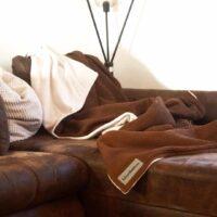 kuscheldecke inbraun auf braunem sofa