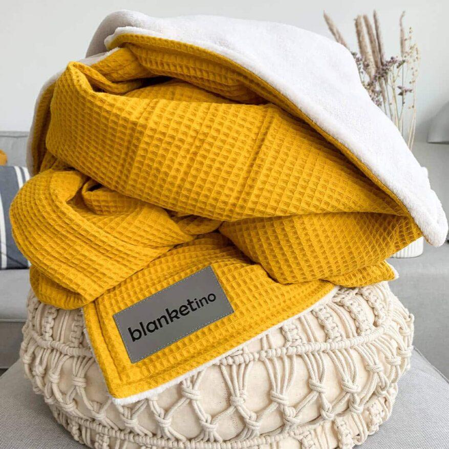moderne einrichtungsideen mit pouf im boho stil und gelber kuscheldecke mit trockenblumen