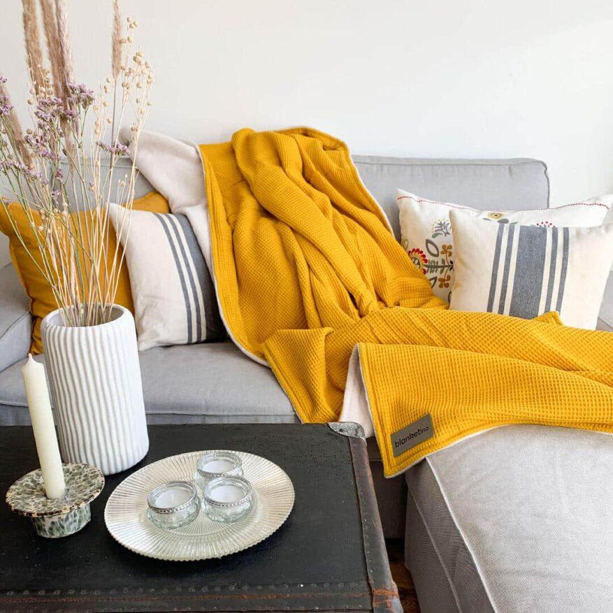 kuscheldecke in gelb im skandinavischen stil auf sofa in grau mit trockenblumen