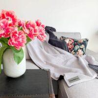 frische-blumen-mit-kuscheldecke-passend-zu-sofa-in-beige