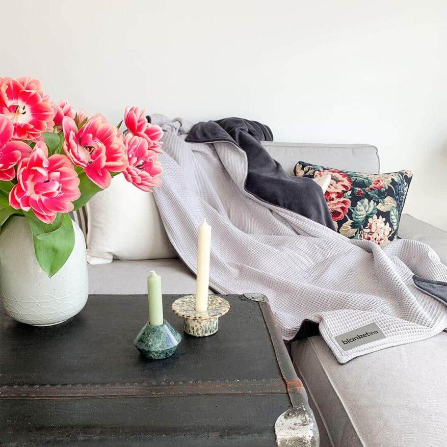 minimalistisches-wohnzimmer-mit-frischen-blumen-und-kuscheldecke-in-silbergrau