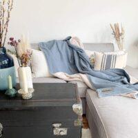 moderne_kuscheldecke_im_skandinavischen_stil_in_wolkenblau_passend_zu_grauem_sofa