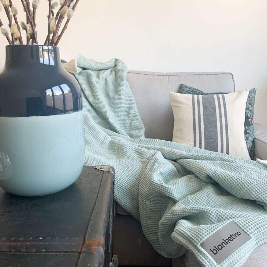 mintfarbene kuscheldecke mit passender deko im wohnzimmer