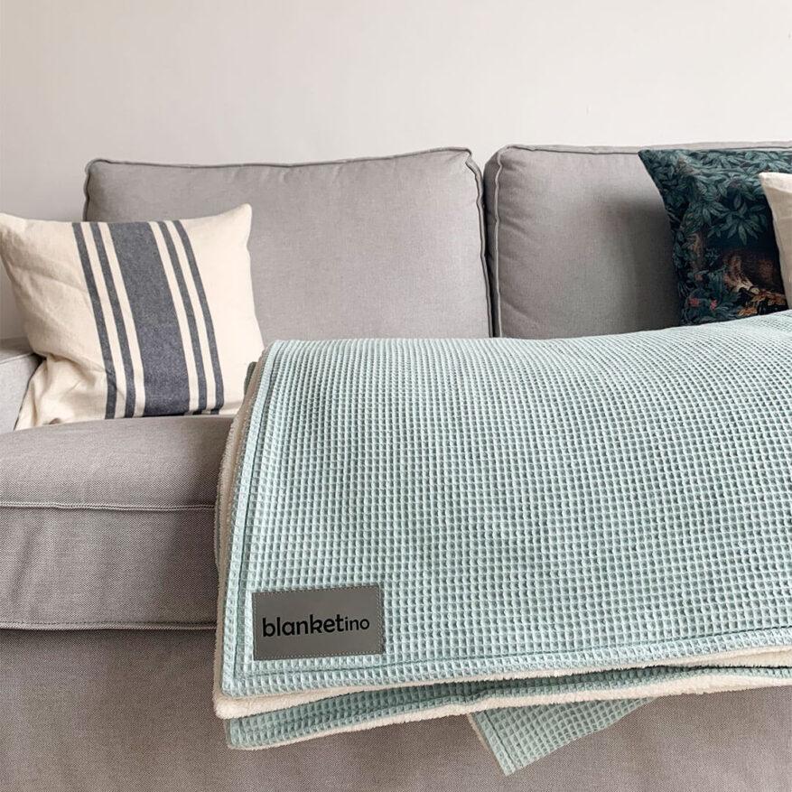 weiche kuscheldecke in mint und sandweiss auf hellgrauem sofa