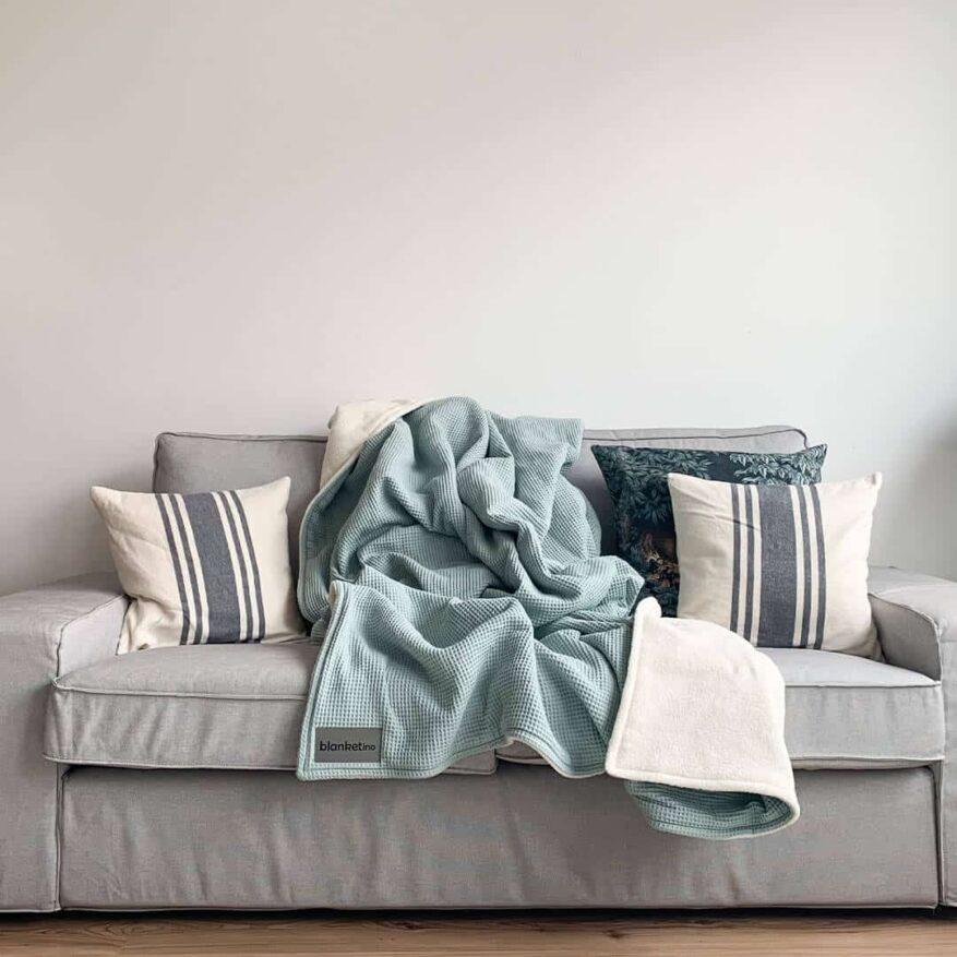 weiche kuscheldecke in mint auf hellgrauem sofa