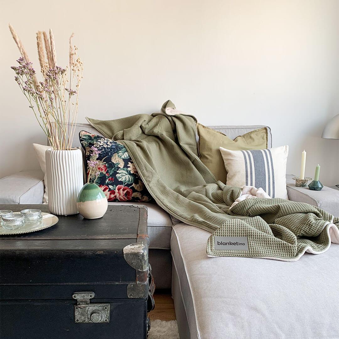 modernes wohnzimmer mit olivfarbener kuscheldecke in gedeckten farben im minimalistischen stil