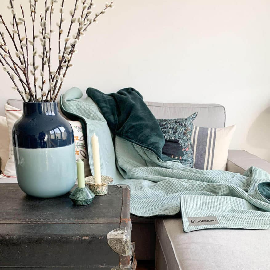moderne kuscheldecke super weich in mintgruen und smaragdgruen auf grauem sofa mit weidenkaetzchen