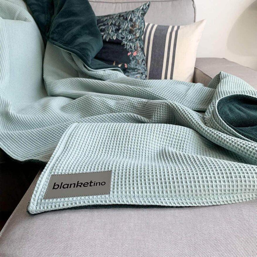 gemuetliche kuscheldecke leicht waschbar passend zu grauem sofa mit kissen
