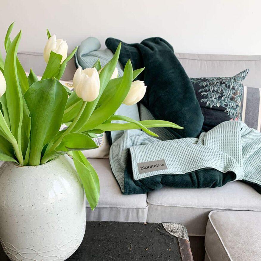 gruene kuscheldecke in mint und smaragdgrün mit tulpen im frühling passend zu grauem sofa