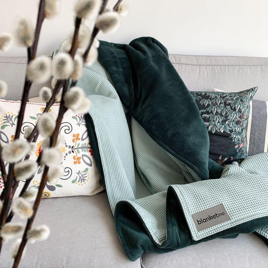 stylische kuscheldecke in mint und dunkelgrün sehr flauschig und warm mit modernen kissen auf grauem sofa