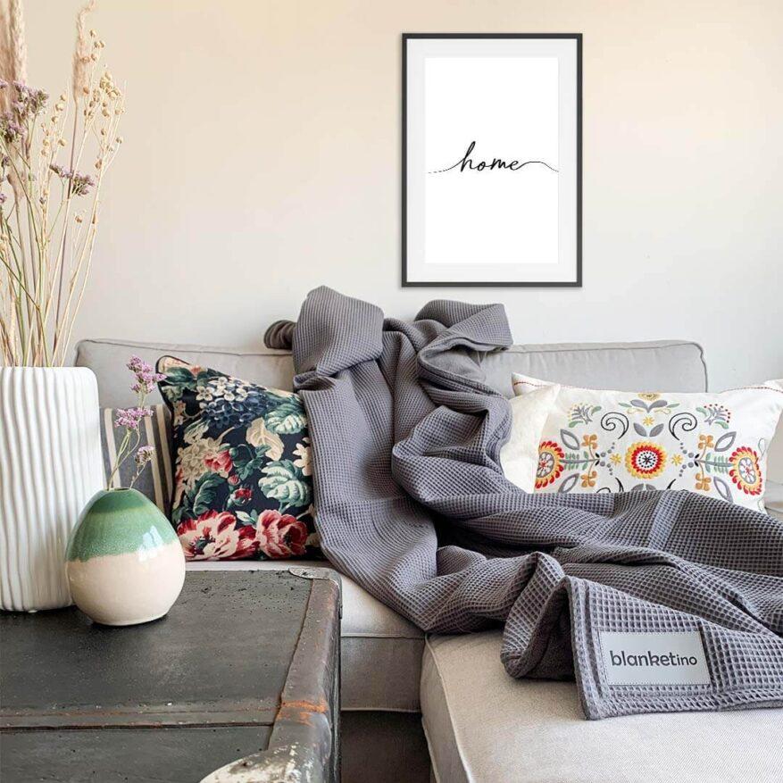 wohnzimmerdekoration mit kuscheldecke und wandbild