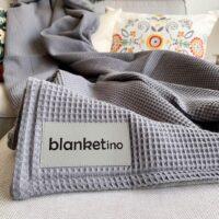 Flauschige Kuscheldecke in grau mit buntem Kissen auf Sofa