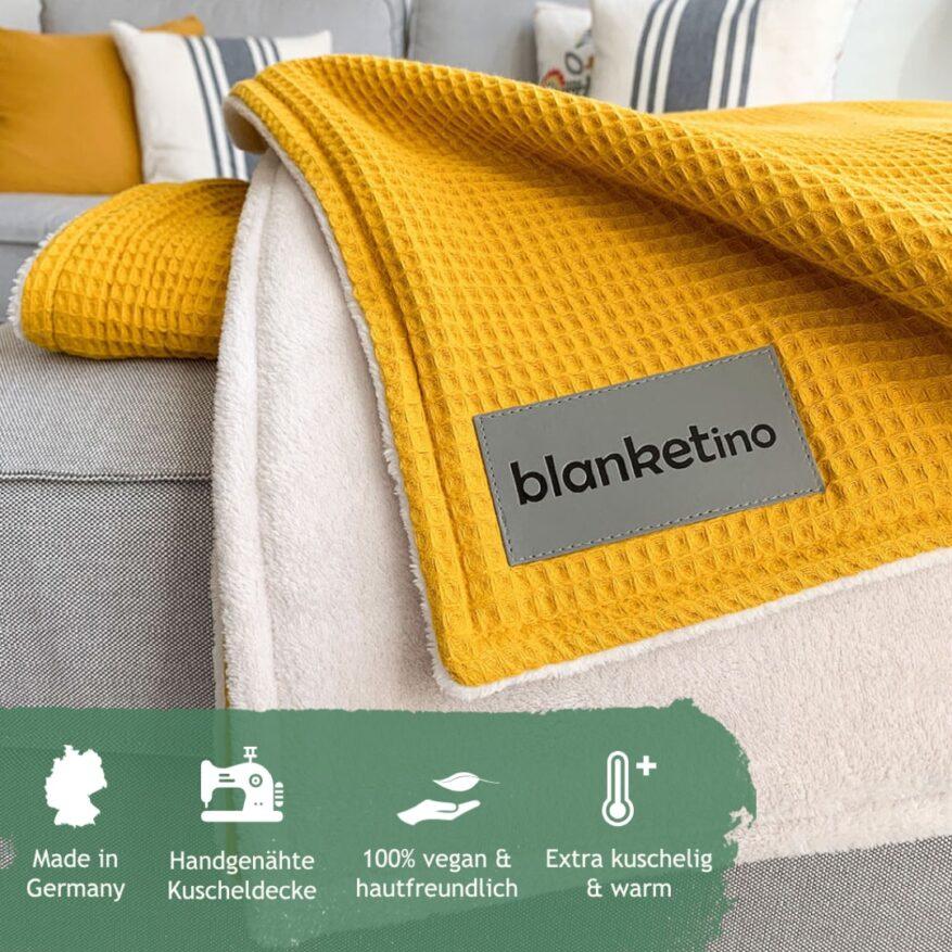 Gelbe Kuscheldecke auf grauem Sofa