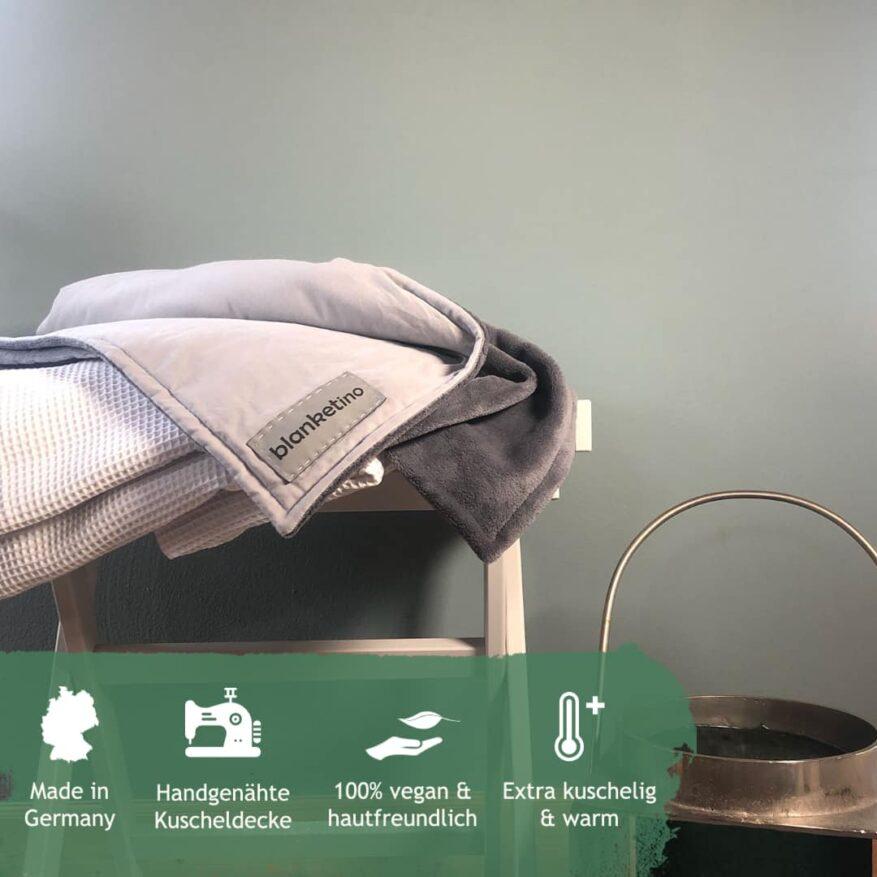 kuscheldecke in grautoenen auf kleinem hocker