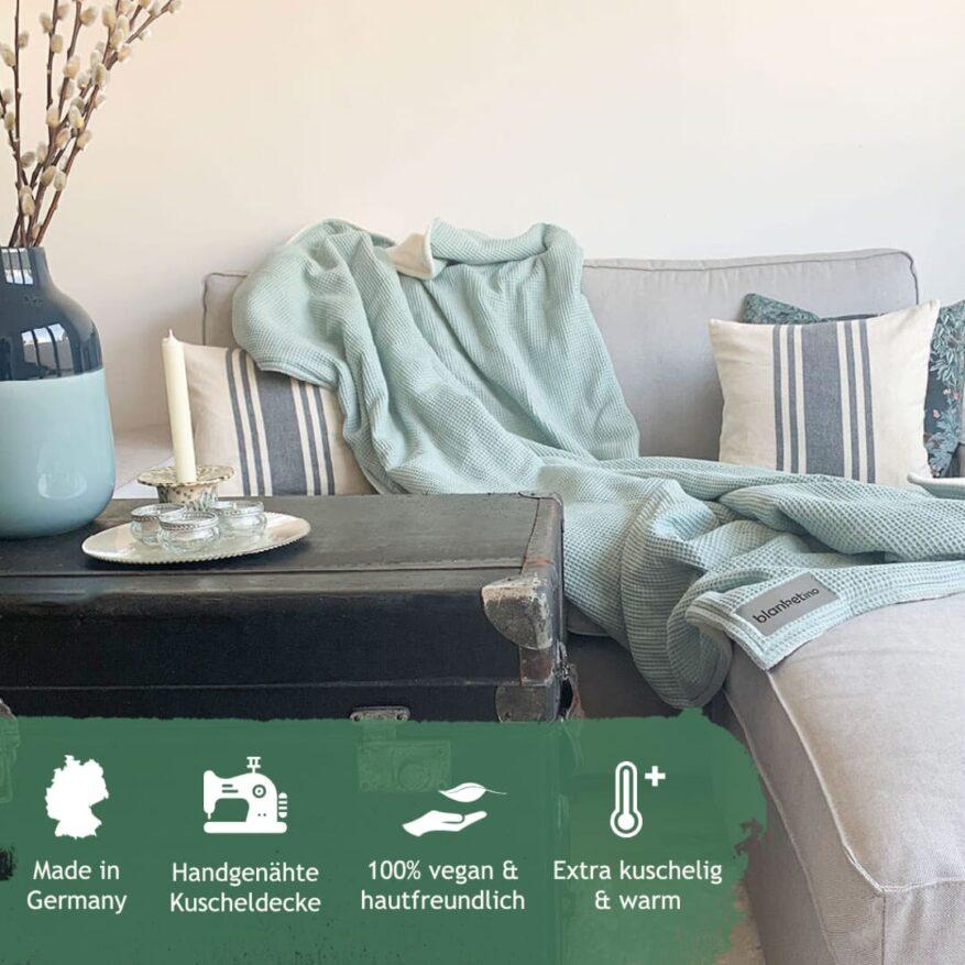 mintfarbene kuscheldecke auf hellgrauem sofa