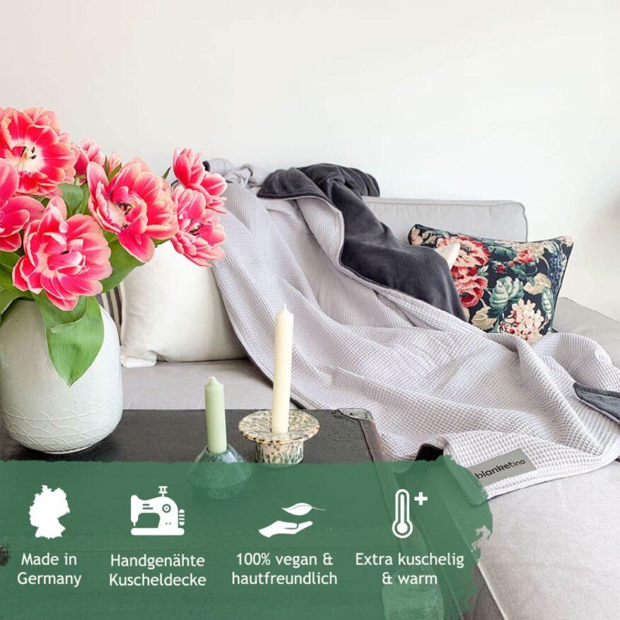 silbergraue kuscheldecke in minimalistischem wohnzimmer