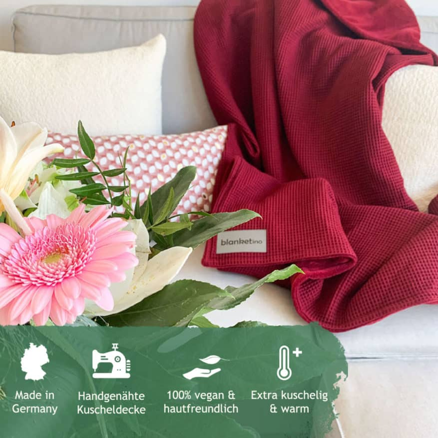 rote kuscheldecke auf hellgrauem sofa